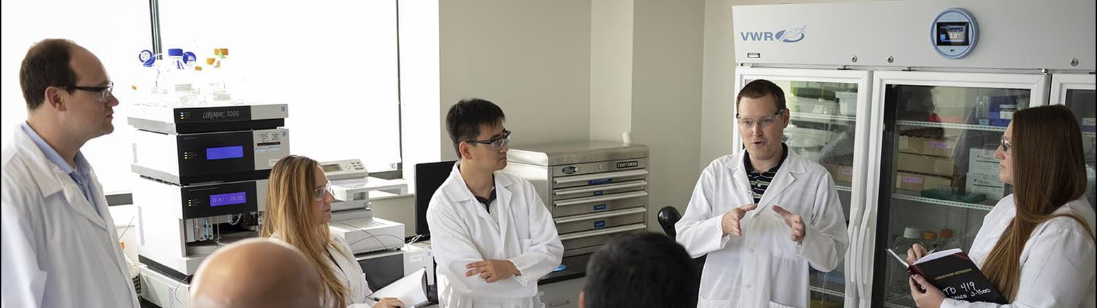 group meeting of scientists in white lab coats